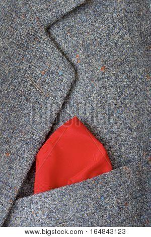 Red handkerchief in the pocket of a tweed jacket.
