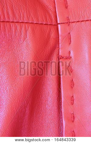 Macro shot of the stitching on a red leather coat.