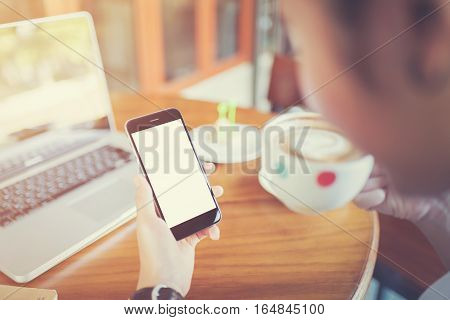 girl using smart phone in cafe. hand holding smart phone white screen. black color smart phone vintage tone. hand holding using mobile phone.