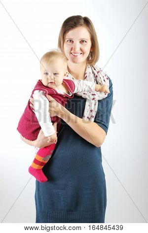 Family, children, people concept. Studio shot of a beautiful mother carrying her adorable baby girl.