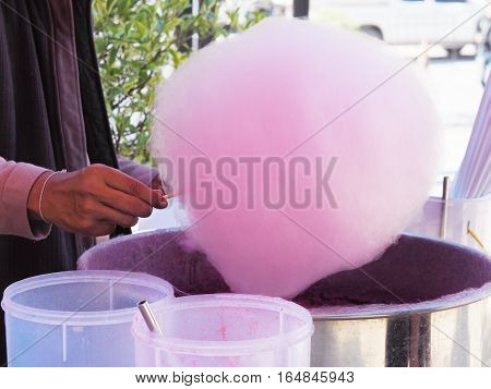 Human hand making sweet pink cotton candy.