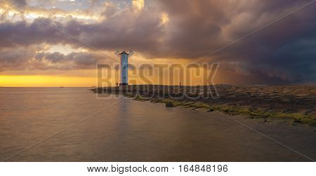 storm passing over the lighthouse at sunset