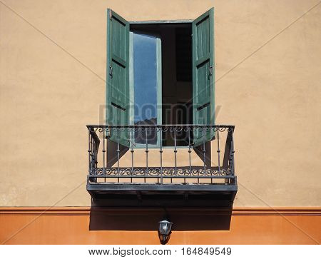 Wooden green window on concrete wall with balcony
