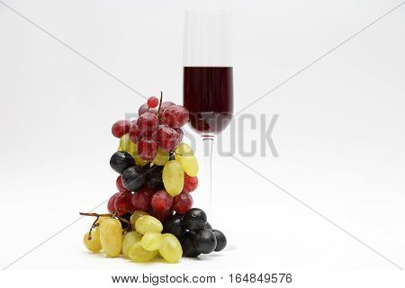 glass with red wine with grapes on a light background