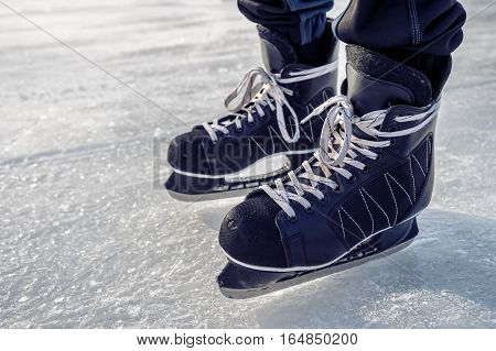 Close-up of ice skating shoes on a rink with people skating in the background (Lafontaine Park Montreal Canada)
