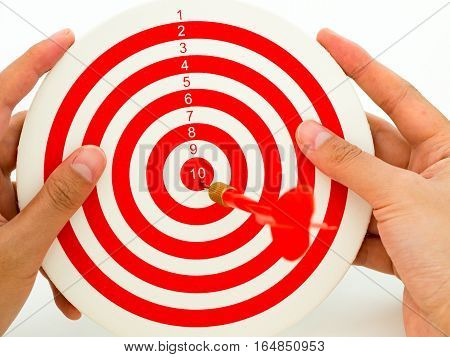 Woman hand holding red dartboard with red bullseye dart arrow hitting target center. Concept of success target goal achievement.