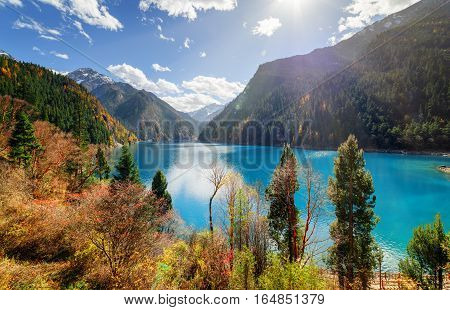 Beautiful View Of The Long Lake With Azure Water Among Mountains