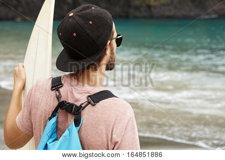 Stylish Young Bearded Surfer Wearing Sunglasses And Snapback Looking At Blue Sea Waves While Standin