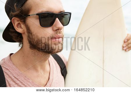 Close Up Portrait Of Handsome Young Man With Fuzzy Beard Wearing Sunglasses And Baseball Cap Backwar