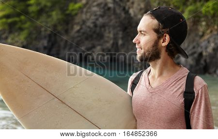 Fashionable Bearded Surfer In Snapback Holding Surfboard Standing On Beach And Looking At Sea, Watch