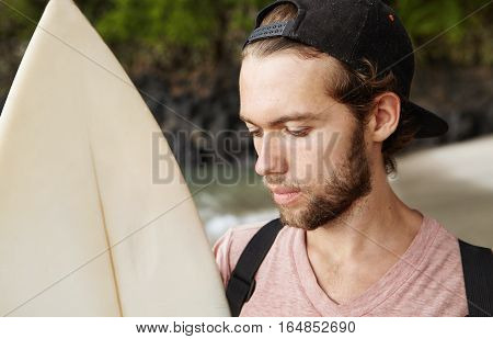 Serious And Concentrated Young Bearded Pro Surfer In Snapback Holding His Surfboard, Making Up His M