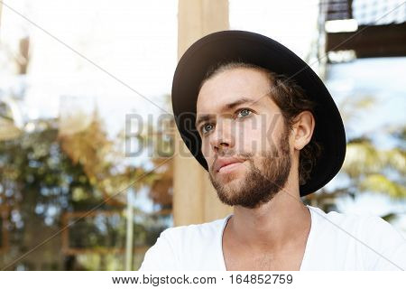 Close Up Portrait Of Good-looking Young Caucasian Hipster With Thick Beard Wearing Black Hat And Whi