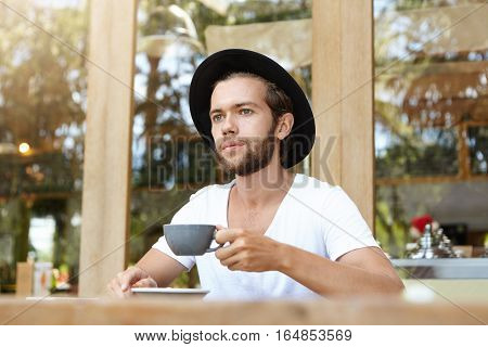 Stylish Young Bearded Man Wearing White T-shirt And Black Hat Holding Cup Of Coffee Or Tea, Enjoying