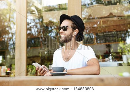 People, Technology And Communication Concept. Stylish Young Bearded Male In Black Sunglasses Holding