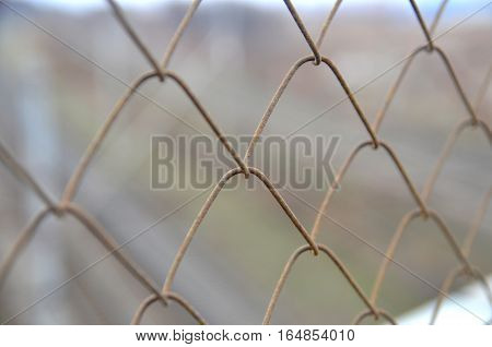 Old rusty chain link grid fence close view prison concept