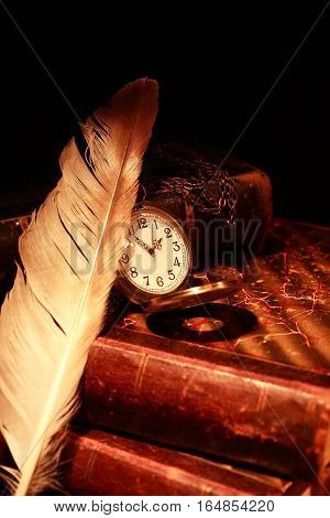 Vintage still life. Quill pen and pocket watch on old book