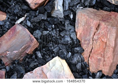 Extinct coals after bonfire surrounded with rocks. Ashes and cinders from waste burning. Black ashes or charcoal texture wallpaper. Burnt wood. black charcoal as background. The ash background.