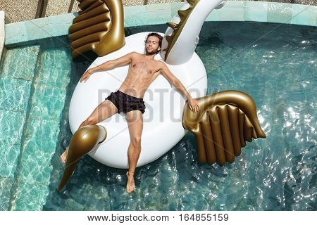 Top View Of Relaxed And Happy Young Shirtless Businessman Floating In Swimming Pool, Lying On Air Be