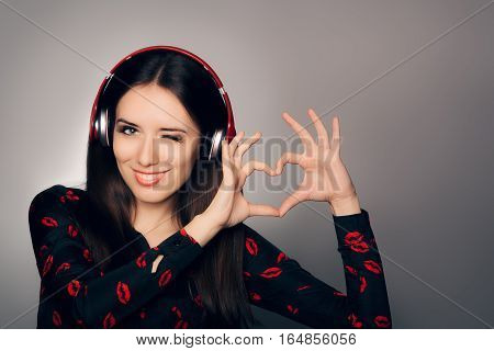 Smiling Girl with Headphones Making Heart Sign