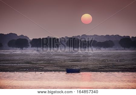 The sun rises over the eastern riverbank of the Ganges River near Varanasi India.