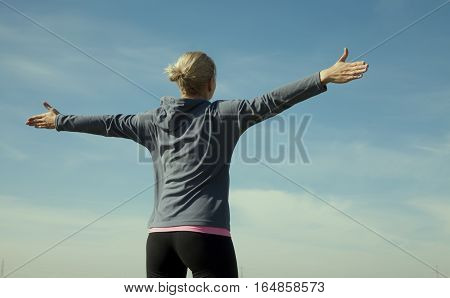 Woman With Arms Raised  Against Blue Sky Bg