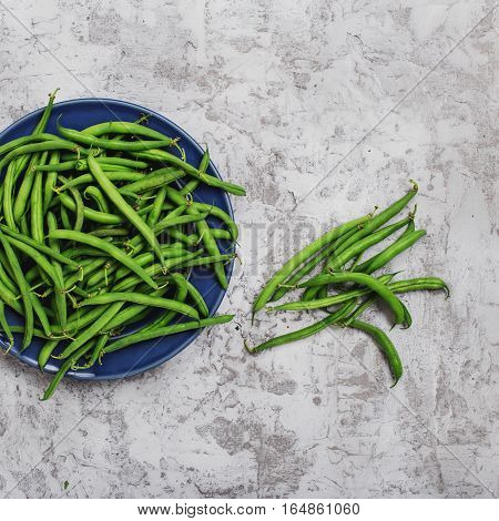 French bean in blue plate on the light gray surface top view