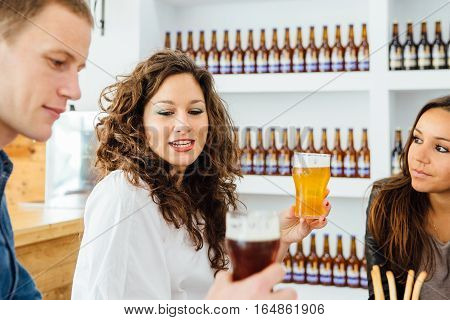 Two women and man talking while holding glasses of craft beer