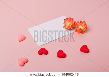 Valentine day composition: credit / visiting card template with spring flowers and small hearts on light pink background.