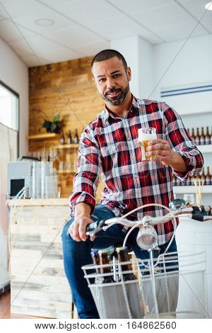 Handsome bearded man in checked shirt with beer on bike indoor
