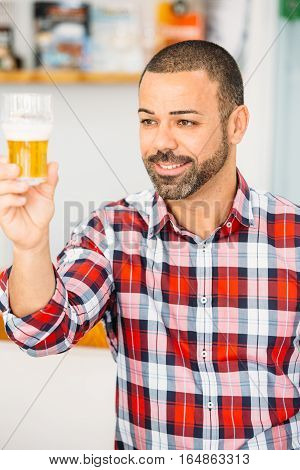 Portrait of bearded man in checked shirt looking at glass of light craft beer