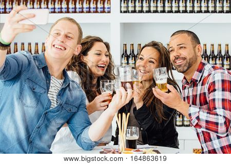 Smiling adult people with craft beer taking selfie with glasses
