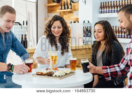 Smiling adult people tasting craft beer while sitting at table with snack board