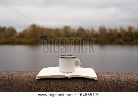 A scene on a river bank with a cup of coffee and a notebook with blank pages.