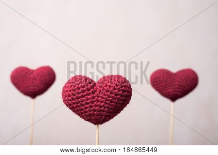 Three crocheted hearts on wooden sticks with a focus on one of them.