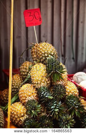 Pile of unpeeled pineapples with price tag at the market counter. Many yellow fruit stacked in a pyramid at the supermarket in Thailand