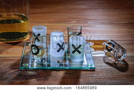 Alcohol wins in xOx game on a wooden table