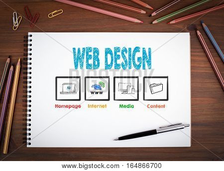 Web Design. Notebooks, pen and colored pencils on a wooden table.