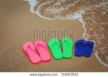 family at beach concept - flip flops at sand beach