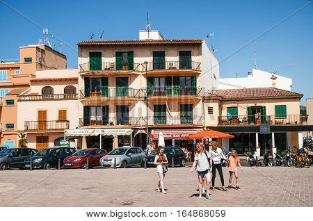 Alcudia Mallorca Spain - May 23 2015: Family of tourists walking along at historical town part of Alcudia with its traditional house and cafe. Carles V square area.