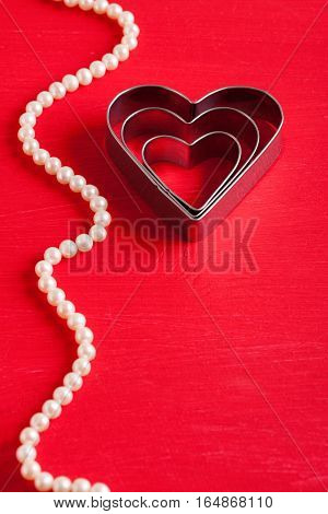 Valentine Background With Metal Hearts On Red Wood.