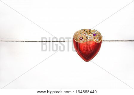 Red heart of glass is decorated with beautiful colorful stones on a white wooden background