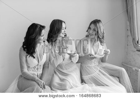 Three bridesmaid sisters in a bright room in lingerie in the morning.