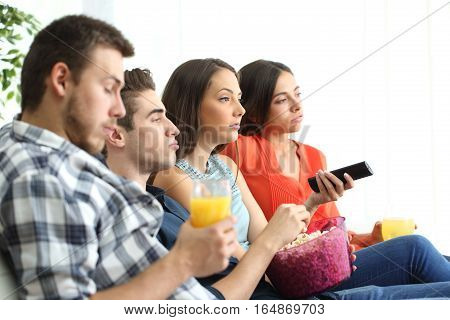 Side view of bored group of four friends watching a bad tv program sitting on a sofa in the livingroom of an apartment