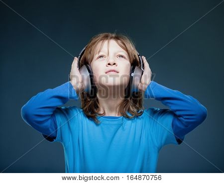 Boy with Blond Hair Listening to Music in Headphones