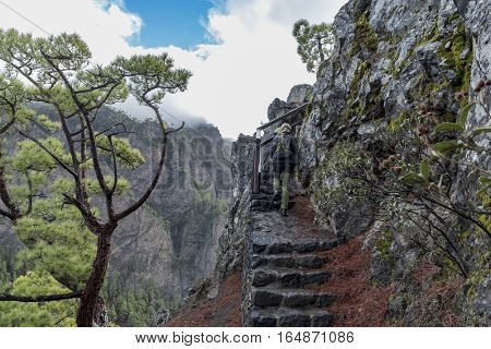"Cumbrecita mountains in the ""Caldera de taburiente"" national park with its characteristic landscape. Photo shows the rocky stairs of a trail with cumbrecita mountains in the background. A female hiker walks up the stairs"