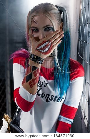 Portrait of smiling girl in costume Harley. She is near grid. She closes her mouth with her hand. Close up. Cosplay.