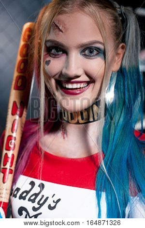 Portrait of smiling girl in costume Harley with crazy eyes. She stands with bat. Close up. Cosplay. poster