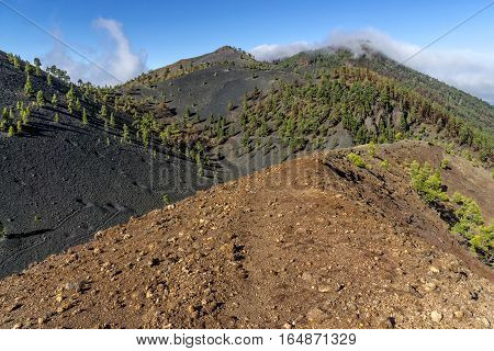 "Shot of the famous trekking path ""Ruta de los vulcanos"" taken in the south of la Palma nearby Los Canarios. The foreground shows the trekking path on the crater rim the background black lava hills."