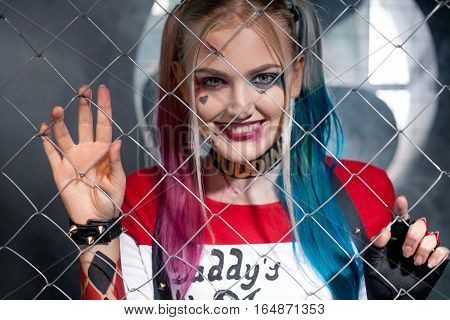 Portrait of smiling girl in costume Harley. She looks through the grid. Close up. Cosplay.