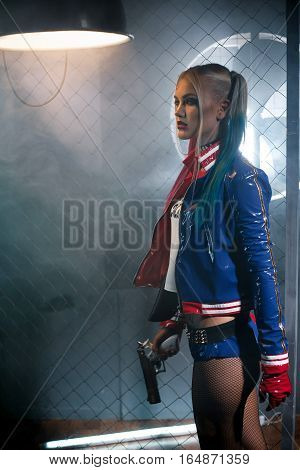 Girl in costume Harley with gun. Cosplay. She stands near grid under the lamp. Cosplay. poster